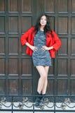 年轻美丽的时髦的妇女在一件红色外套,灰色穿戴了被编织的礼服,黑起动,以一个木门为背景 Str 免版税库存图片