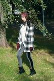 年轻美丽的时髦的妇女,穿在一只白色和黑笼子的一件外套,白色夹克,灰色长裤,黑起动 街道样式, s 免版税库存图片