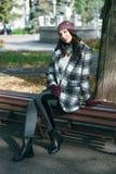 年轻美丽的时髦的妇女,穿在一只白色和黑笼子的一件外套,白色夹克,灰色长裤,黑起动 街道样式, s 免版税库存照片