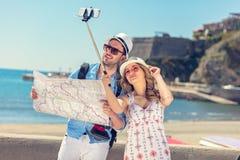 年轻美丽的朋友旅游夫妇和一起拍selfie棍子照片在镇里愉快在晴天 免版税库存照片