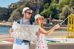 年轻美丽的朋友旅游夫妇和一起拍selfie棍子照片在镇里愉快在晴天 库存照片