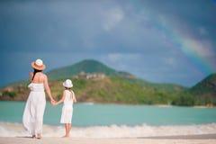 年轻美丽的母亲和她可爱的矮小的女儿获得乐趣在热带海滩 库存图片