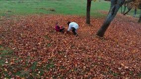 年轻美丽的母亲和她的年轻女儿获得乐趣在他们跳跃并且投掷叶子入空气的秋天森林 影视素材