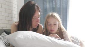 年轻美丽的母亲和她逗人喜爱的女儿在片剂做网络购物和微笑,当说谎在床在时 股票视频