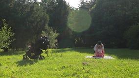 年轻美丽的母亲简而言之和玻璃步行在绿色草坪有她的女婴的