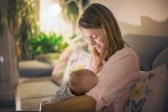 年轻美丽的母亲,哺乳她新出生的男婴 免版税图库摄影