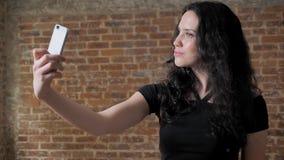 年轻美丽的深色的女孩在她的智能手机做selfie,摆在,通信构想,砖背景 股票视频