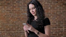 年轻美丽的深色的女孩在她的智能手机,通信概念,砖backgroung发短信 股票录像