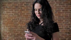 年轻美丽的深色的女孩观看在她的智能手机,微笑,通信概念,砖backgroung的照片 影视素材