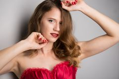 年轻美丽的深色的妇女的面孔黑暗的背景的在红色 库存图片