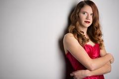 年轻美丽的深色的妇女的面孔黑暗的背景的在红色 免版税库存图片