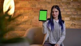年轻美丽的白种人女性特写镜头画象使用片剂和显示绿色屏幕的对照相机在舒适家 股票录像