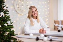 年轻美丽的白肤金发的在居住ro的妇女包装的圣诞礼物 库存图片