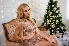 年轻美丽的白肤金发的在葡萄酒沙发o的妇女饮用的香槟 免版税库存照片