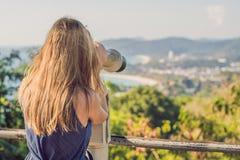 年轻美丽的白肤金发的妇女享受与的看法投入硬币后自动操作的双筒望远镜 水和天空是蓝色的 她佩带  免版税库存照片