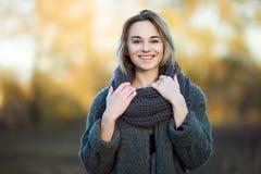 年轻美丽的白肤金发的妇女室外生活方式照片秋天秋天公园舒适围巾灰色葡萄酒外套的 影片过滤器作用 图库摄影