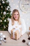 年轻美丽的白肤金发的妇女画象有圣诞礼物的 库存图片