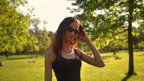年轻美丽的红发女性在自然的夏天投入墨镜 股票视频