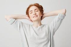 年轻美丽的红头发人女孩画象有闭合的眼睛微笑的享用的在白色backround 在现有量题头之后 免版税库存照片