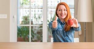 年轻美丽的红头发人妇女在家 免版税库存照片
