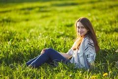 年轻美丽的红头发人妇女坐一个绿色草甸,看照相机 免版税图库摄影