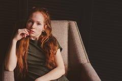年轻美丽的红头发人行家妇女没有做在家放松 库存图片