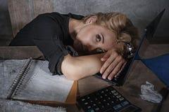年轻美丽的被注重的和哀伤的白肤金发的妇女与感觉疲倦的开会的便携式计算机一起使用在pap淹没的办公桌 免版税图库摄影