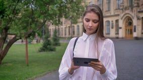 年轻美丽的被集中的女孩在她的片剂工作在夏天,通信概念 股票视频