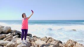 年轻美丽的适合的女孩藏品电话和做selfie照片,当站立在岩石海岸波浪时飞溅在岩石 股票视频