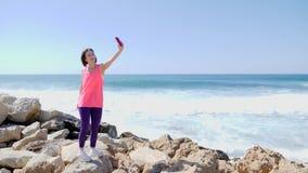 年轻美丽的适合的女孩藏品电话和做selfie照片,当站立在岩石海岸波浪时飞溅在岩石 ? 影视素材