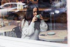 年轻美丽的逗人喜爱的深色的女孩画象灰色毛线衣饮用的咖啡的 免版税库存图片