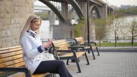 年轻美丽的金发碧眼的女人在智能手机写一则消息 年轻女人基于在堤防的一条长凳  影视素材