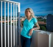 年轻美丽的金发碧眼的女人夏天画象一个高楼的屋顶的 穿绿松石T恤杉和牛仔裤 腋窝 免版税库存图片