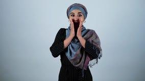 年轻美丽的阿拉伯妇女震惊接触她的面孔用在被隔绝的白色背景的两只手 股票录像