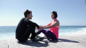 年轻美女亲吻嘴唇的适合的嬉戏人在海滩,当坐时 股票录像