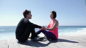年轻美女亲吻嘴唇的适合的嬉戏人在海滩,当坐时 t 股票录像
