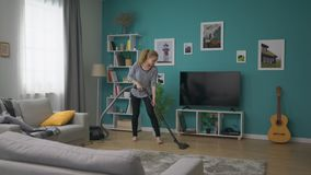 年轻美女吸尘她的舒适公寓的跟踪 影视素材