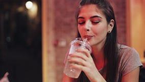 年轻美女喝坐在酒吧或餐馆的鸡尾酒在霓虹标志附近 股票视频