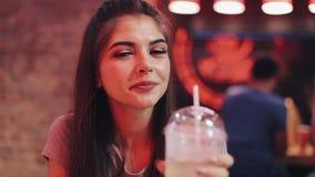 年轻美女喝坐在酒吧或餐馆的鸡尾酒在霓虹标志附近 股票录像