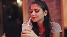 年轻美女喝坐在酒吧或餐馆的鸡尾酒在霓虹标志附近 影视素材