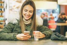 年轻美女在一咖啡厅的喝一份咖啡,当键入在流动智能手机使用应用闲谈时 免版税库存照片