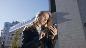 年轻美女在城市和用途智能手机走 发短信在的俏丽的微笑的女孩的画象 影视素材