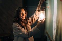 年轻美女在她的手上拿着一个小壁灯 免版税库存图片