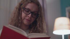 年轻美女在她的舒适客厅读一个法院记录在晚上 股票录像