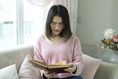 年轻美女在长沙发读一本书 库存照片