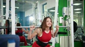 年轻美女提高在健身房的标准并且在头附近采取金属杆 影视素材