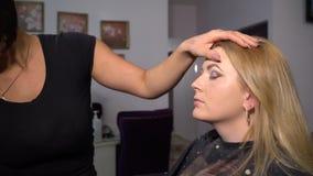 ( 年轻美女模型在椅子坐 化妆师做女孩构成 化妆师 股票录像