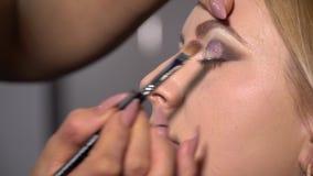 ( 年轻美女模型在椅子坐 化妆师做女孩构成 化妆师 股票视频