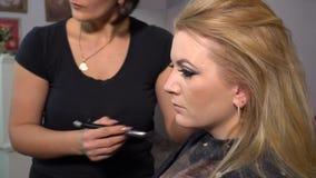 ( 年轻美女模型在椅子坐 化妆师做女孩构成 r 影视素材