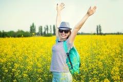 年轻美女沿一块花田走在一好日子 免版税库存图片